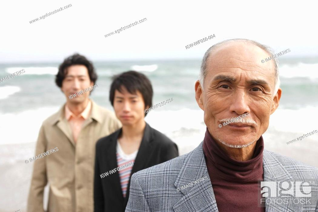 Stock Photo: Grandfather smiling while father and son standing in background, portrait.