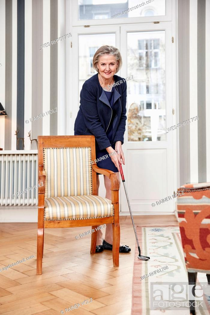 Stock Photo: Senior woman playing golf at home.