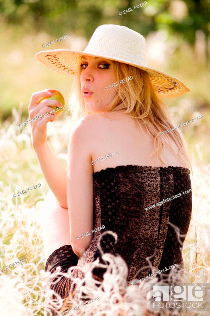 Stock Photo: Young blonde woman with apple sitting in green grass.