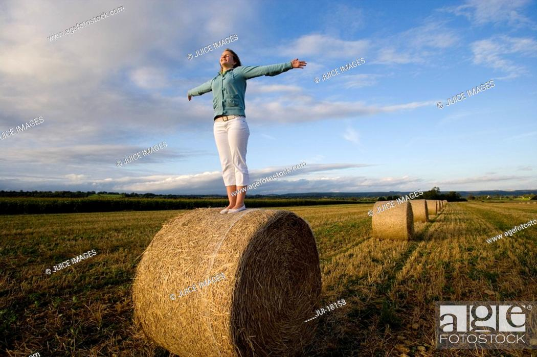 Stock Photo: Teenage girl 16-18 standing on bale of hay in field with arms outstretched.