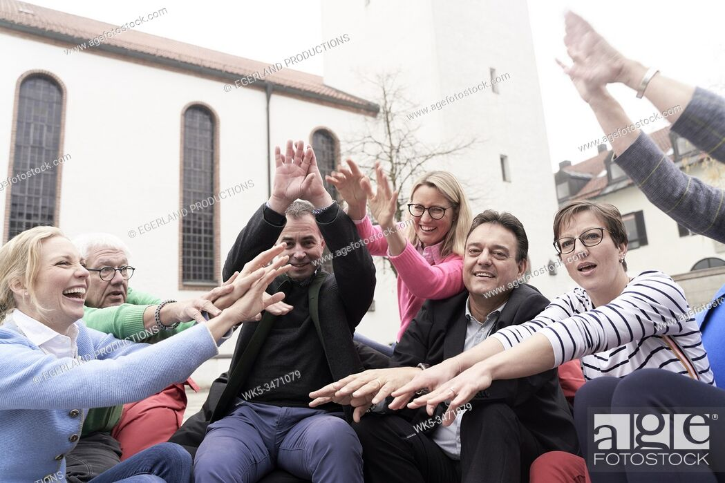 Stock Photo: Group of friends rising hands together.
