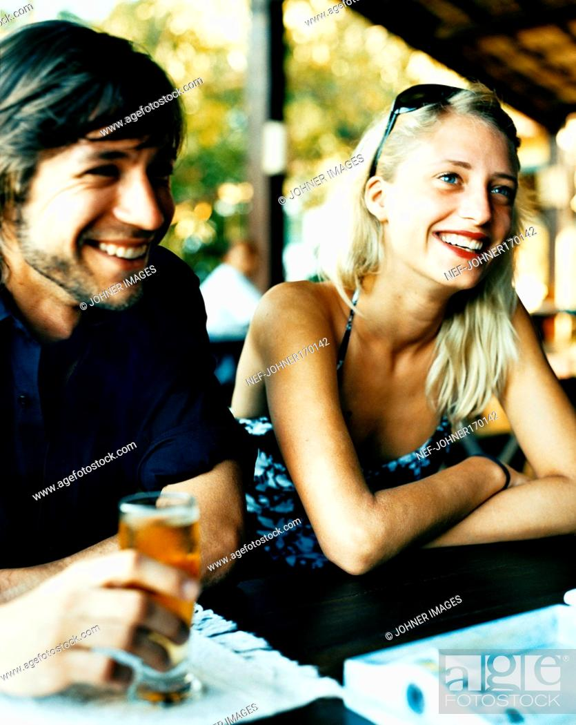 Stock Photo: A smiling young man and woman in an open-air cafe.