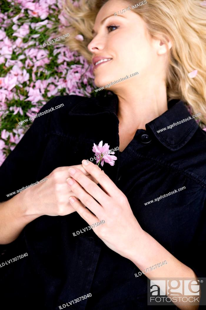 Stock Photo: A mid adult woman lying on the grass, holding spring blossom.
