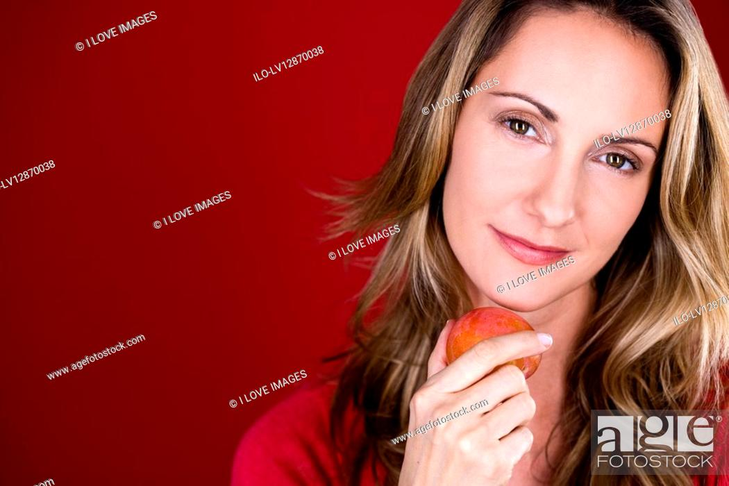 Stock Photo: A mid adult woman holding a plum.