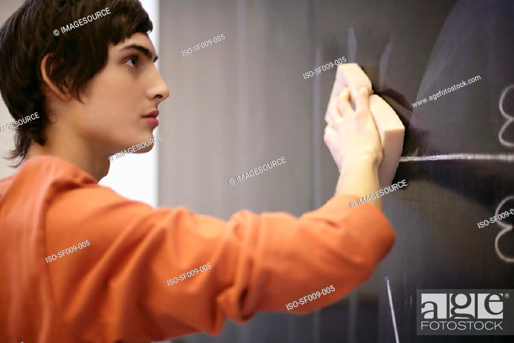 Stock Photo: Young man wiping a blackboard.