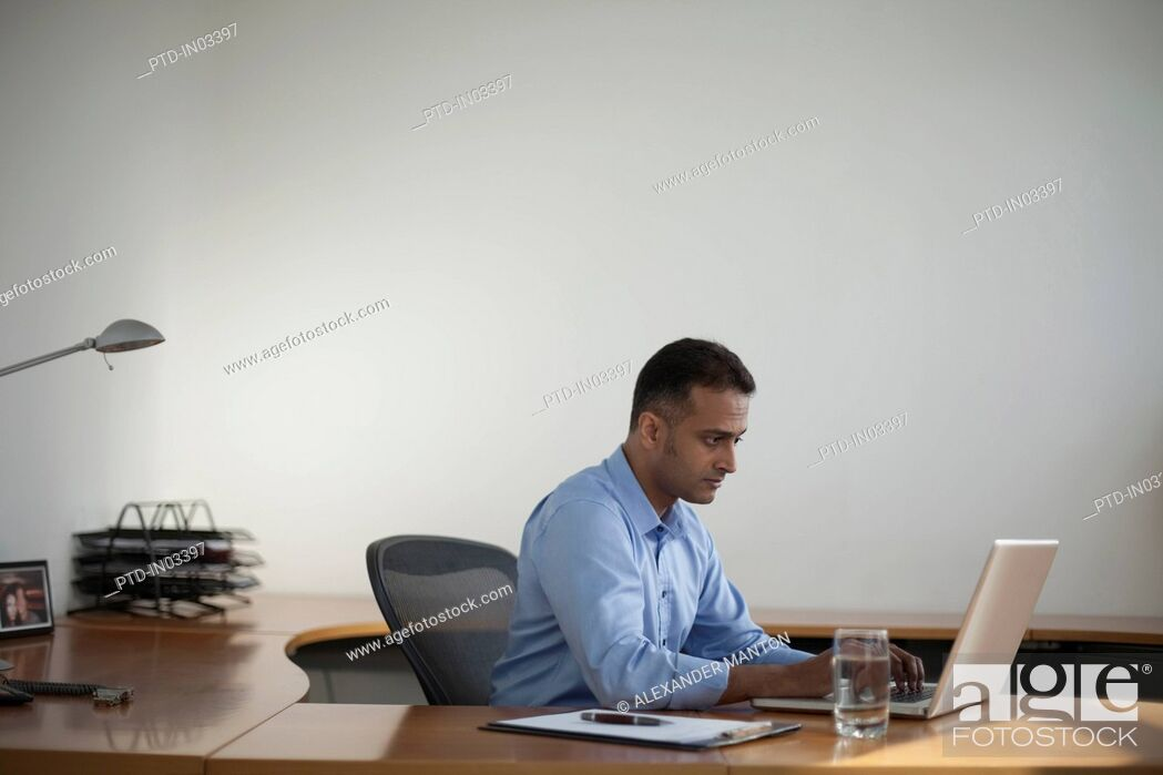 Stock Photo: Singapore, Businessman working at laptop in office.
