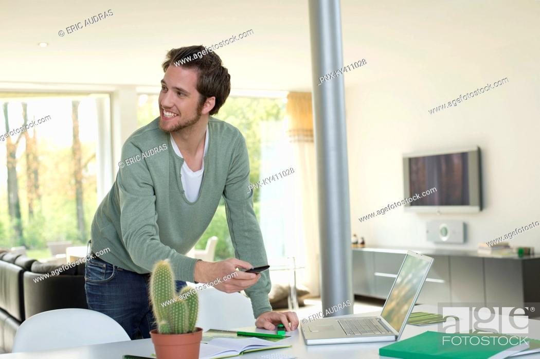 Stock Photo: Man holding a mobile phone and working on a laptop.