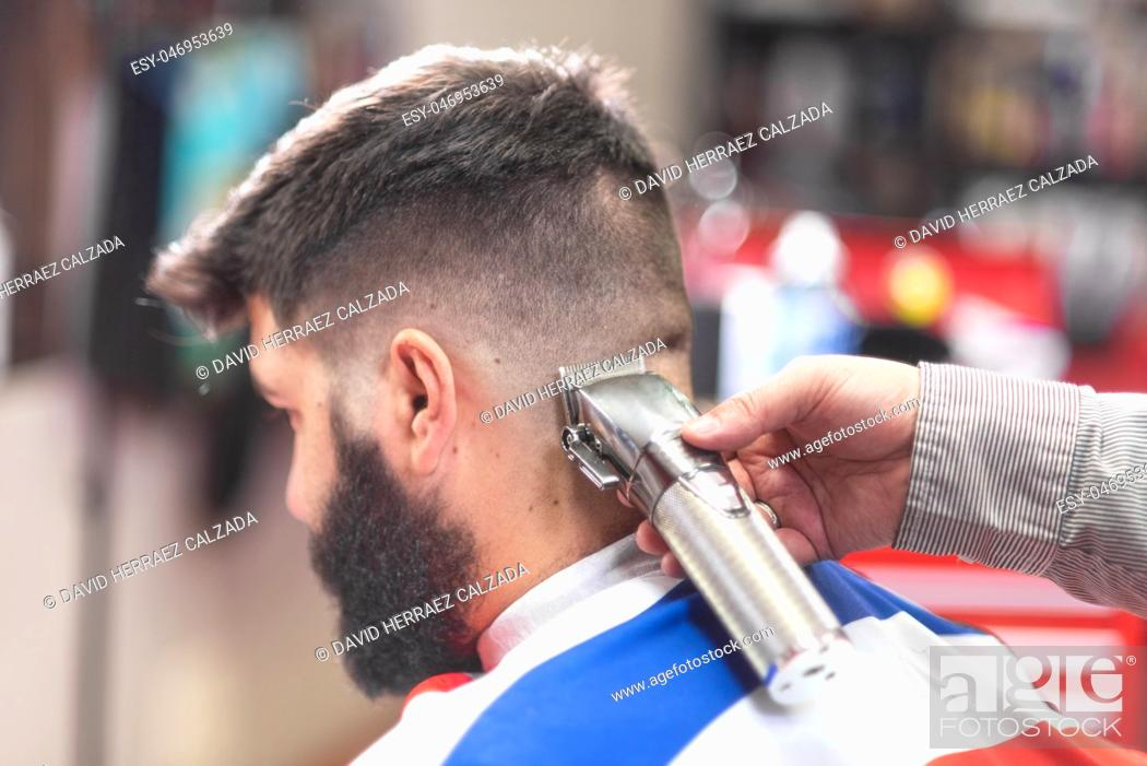 Stock Photo: Handsome bearded man, getting haircut by barber, with electric trimmer at barbershop .