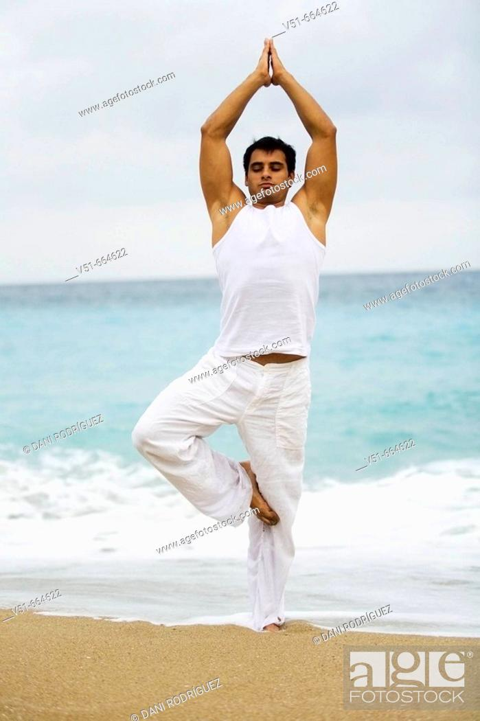 Stock Photo: Young man practising yoga on the beach.
