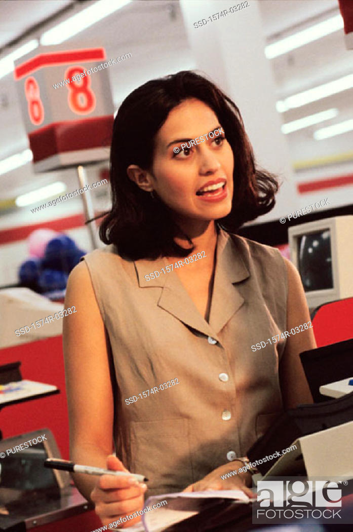 Stock Photo: Young woman standing in front of a checkout counter in a shopping mall.