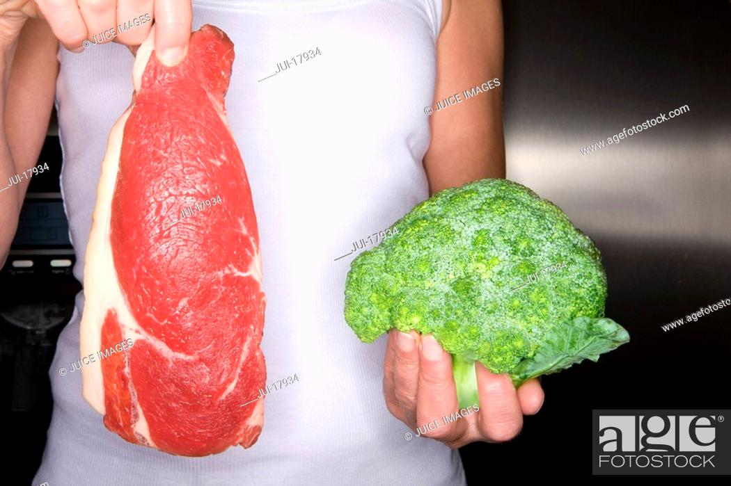 Stock Photo: Close up of woman holding fresh meat and frozen broccoli.