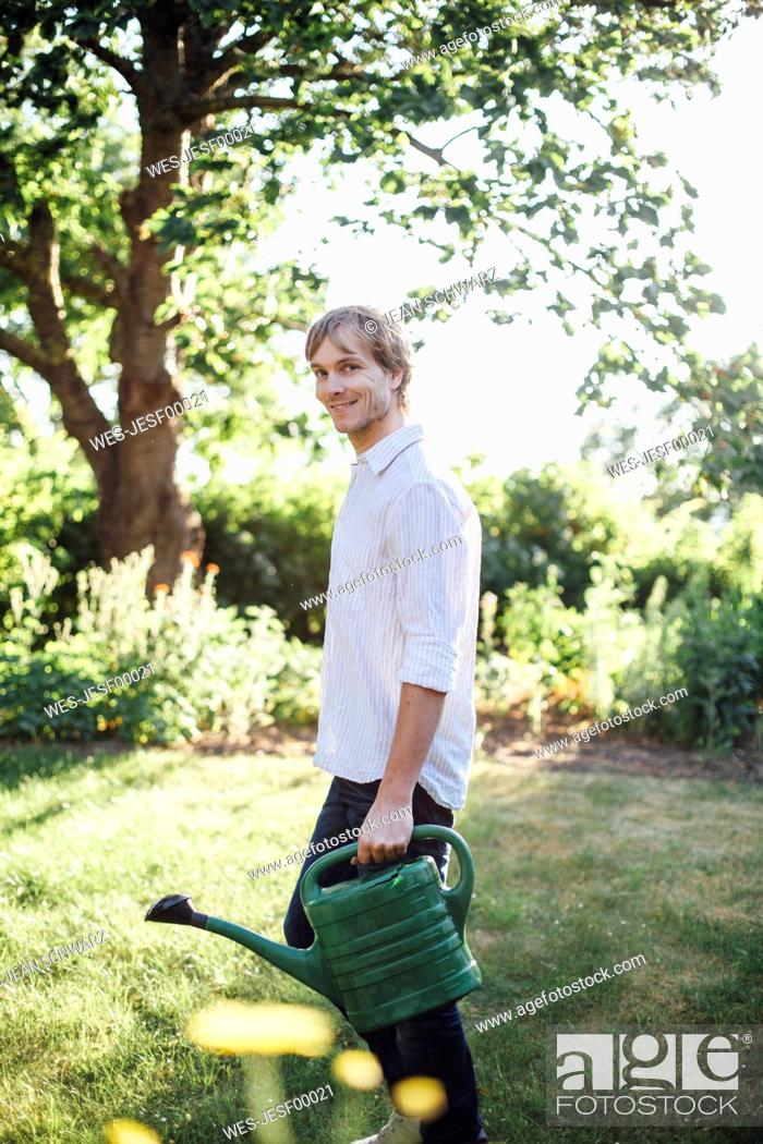 Stock Photo: Man with watering can in garden.