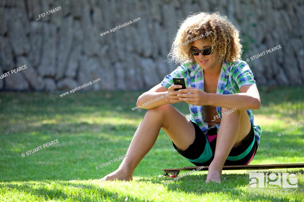 Stock Photo: Teenage boy using his smart phone.