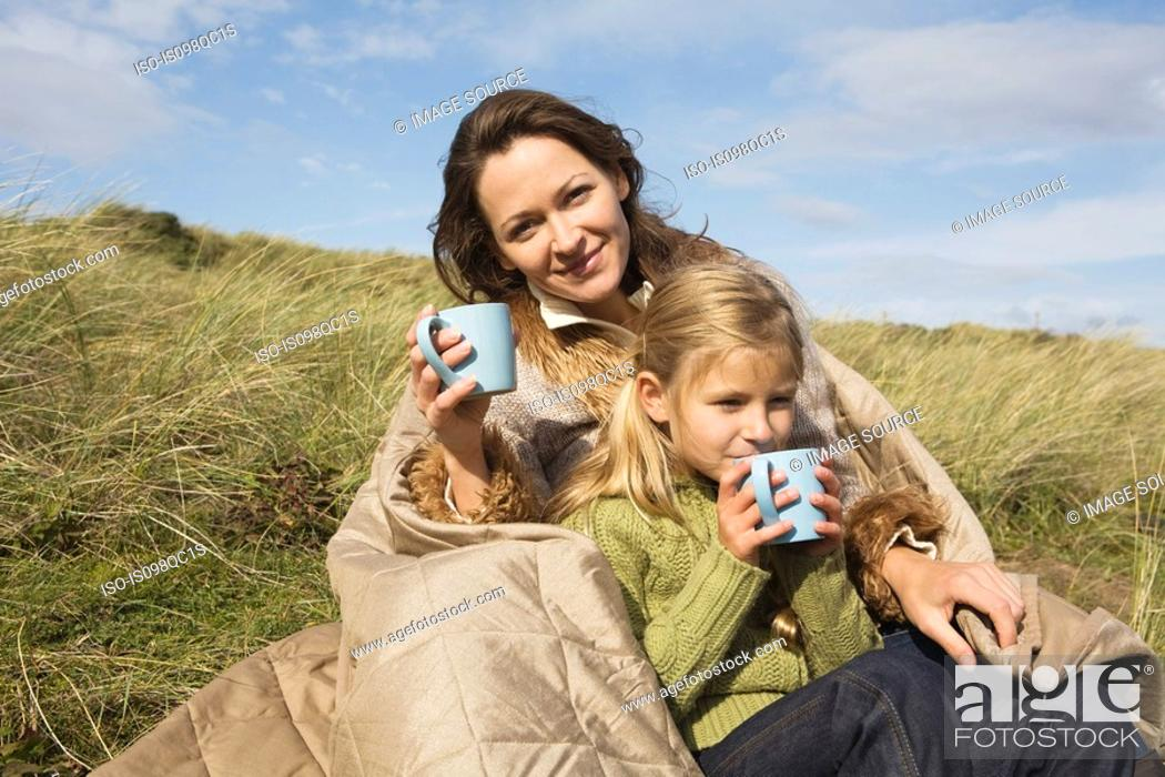 Stock Photo: Mother and daughter outdoors with drinks.