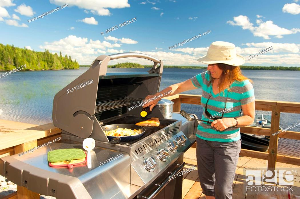 Stock Photo: A woman cooks a meal on a barbeque on a deck overlooking a beautiful lake; Ontario, Canada.