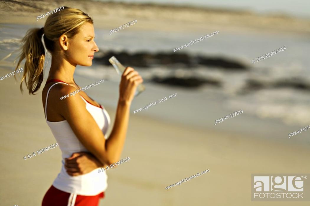 Stock Photo: Young woman standing on beach, drinking water from a bottle.
