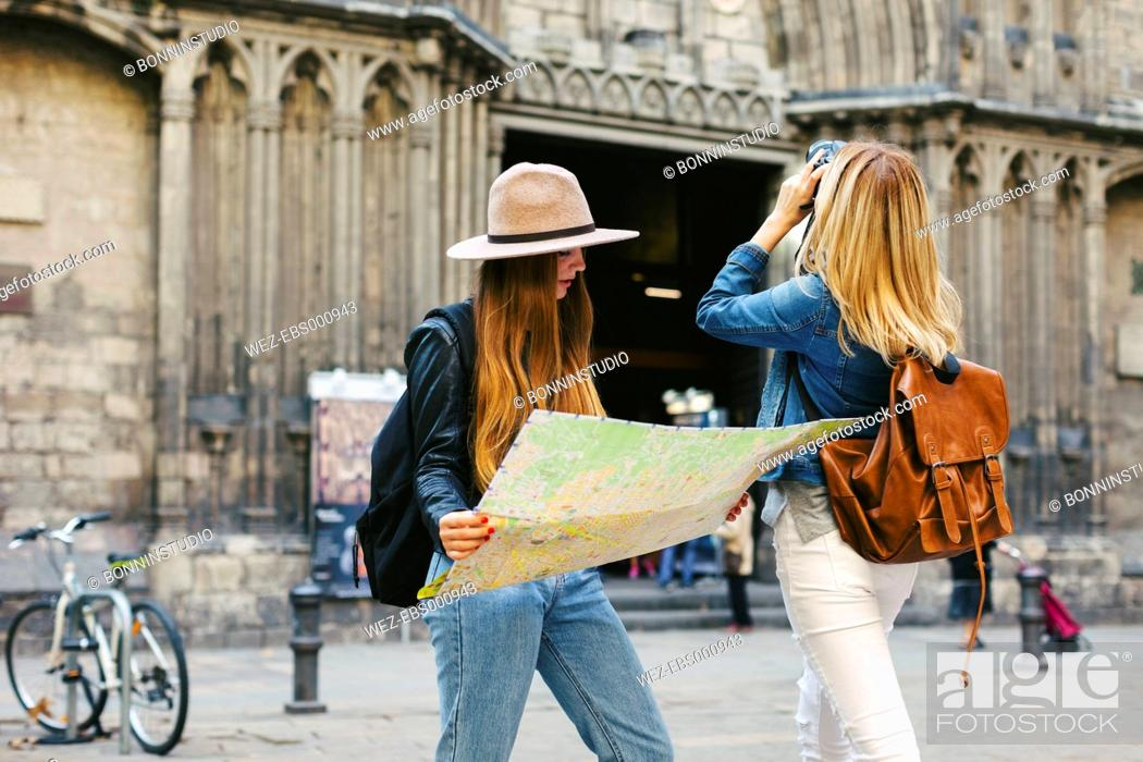 Imagen: Spain, Barcelona, two young women on square with camera and map.
