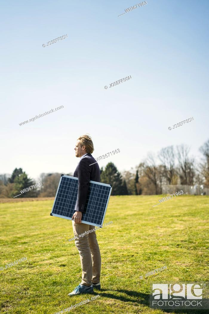 Stock Photo: Male entrepreneur holding solar panel while looking away at park on sunny day.