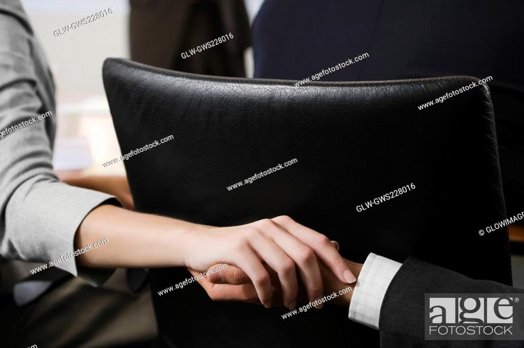 Stock Photo: Close-up of a man's hand holding a woman's hand behind a chair in an office.