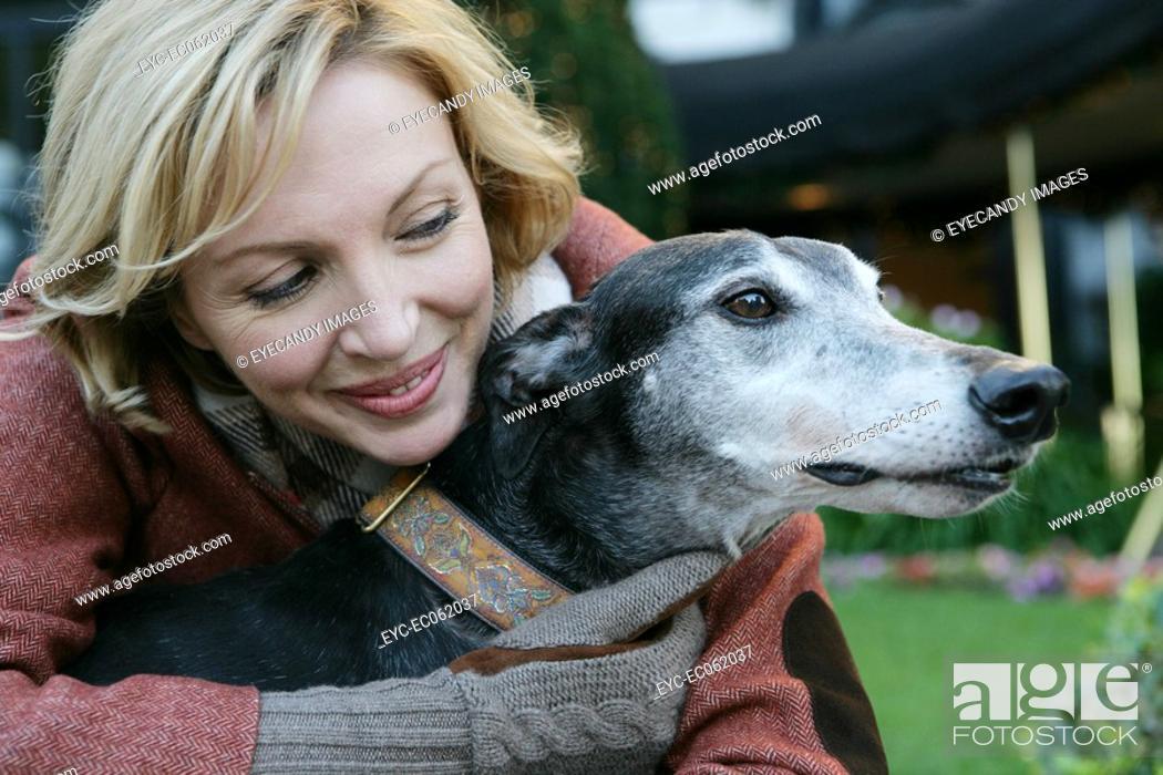 Stock Photo: Mature woman hugging a dog.