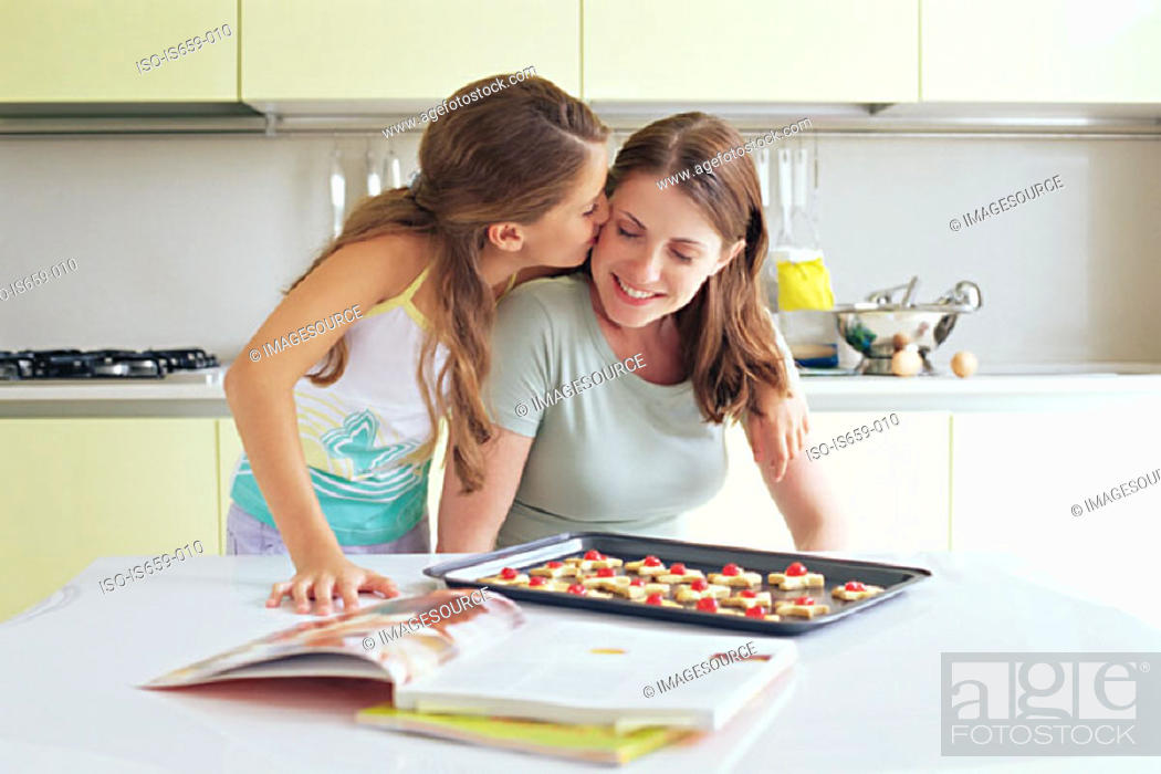 Stock Photo: Girl kissing mother on the cheek.
