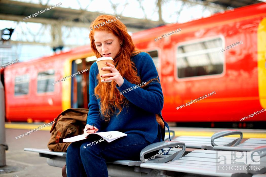 Stock Photo: Woman on bench on train station platform, London.