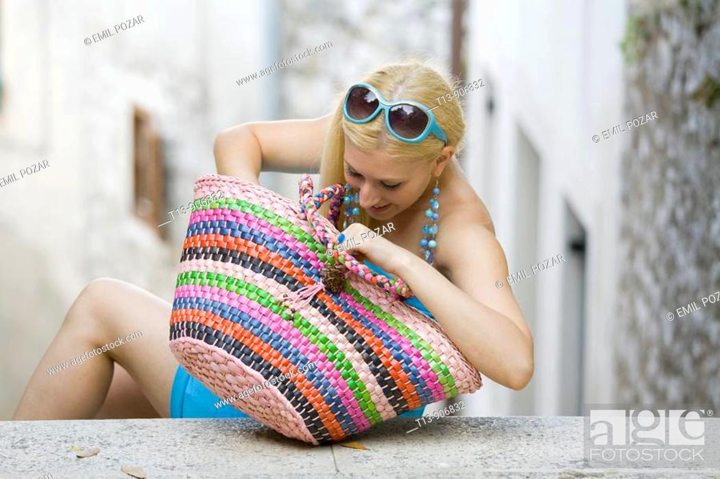 Stock Photo: Young woman is searching in big colourful bag.