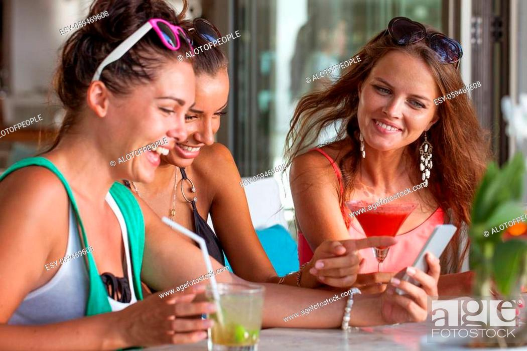 Stock Photo: Three friends amazed watching a smart phone sitting in cafe drinking cocktails.