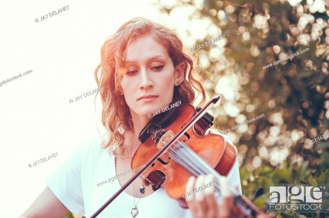 Photo de stock: Confident beautiful woman playing violin against plants.