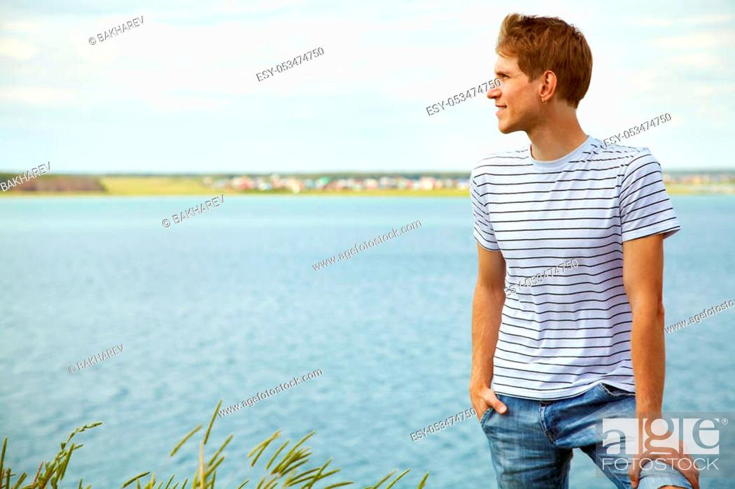 Stock Photo: Portrait of a young smiling man on nature background. good looking man summer outdoors.