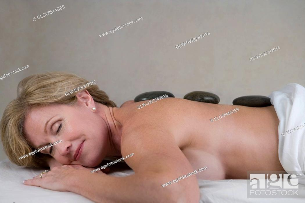 Stock Photo: Side profile of a mature woman lying on a massage table with her eyes closed.