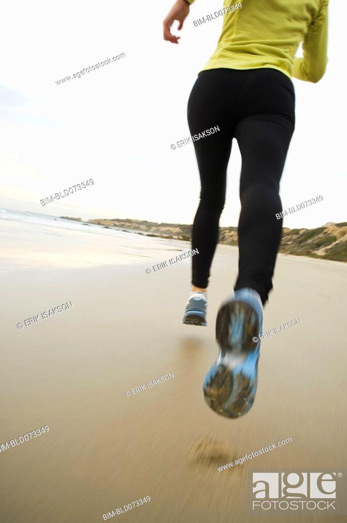Stock Photo: Hispanic woman running on beach.