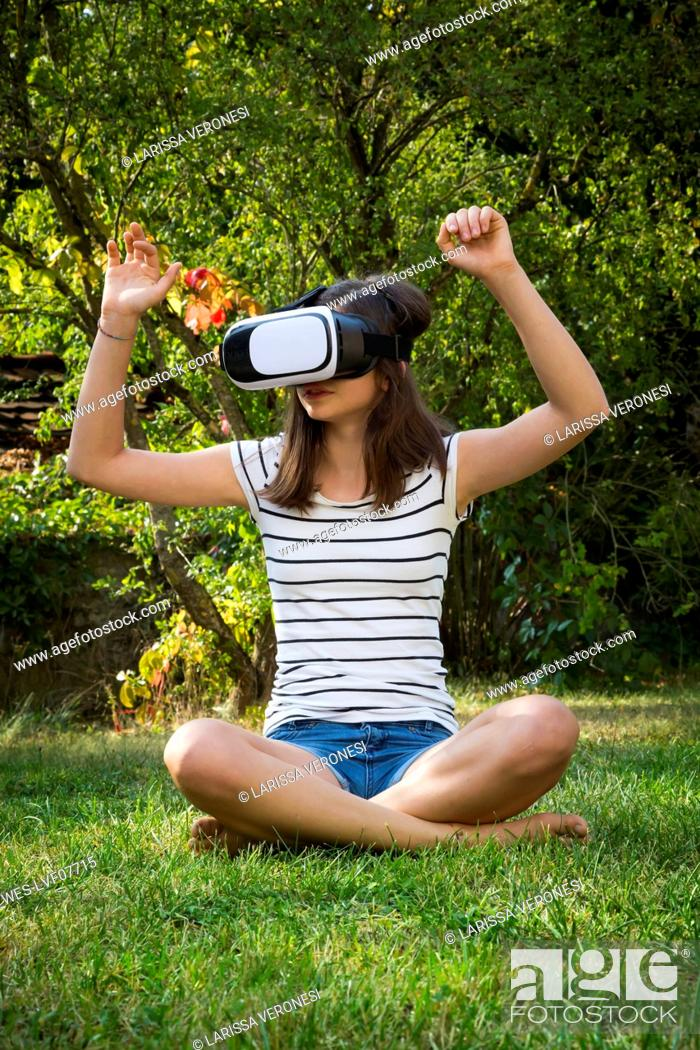 Stock Photo: Girl sitting on meadow in the garden using Virtual Reality Glasses.