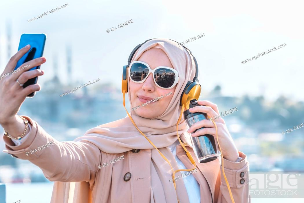 Stock Photo: Beautiful Muslim woman in headscarf and fashionable modern trendy clothes with headphones, smartphone and sunglasses takes selfie.