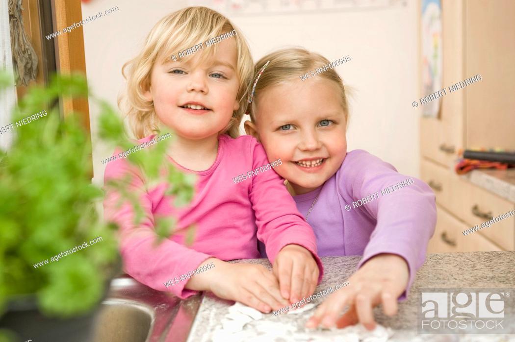 Stock Photo: Girls rolling dough on kitchen worktop, smiling, portrait.