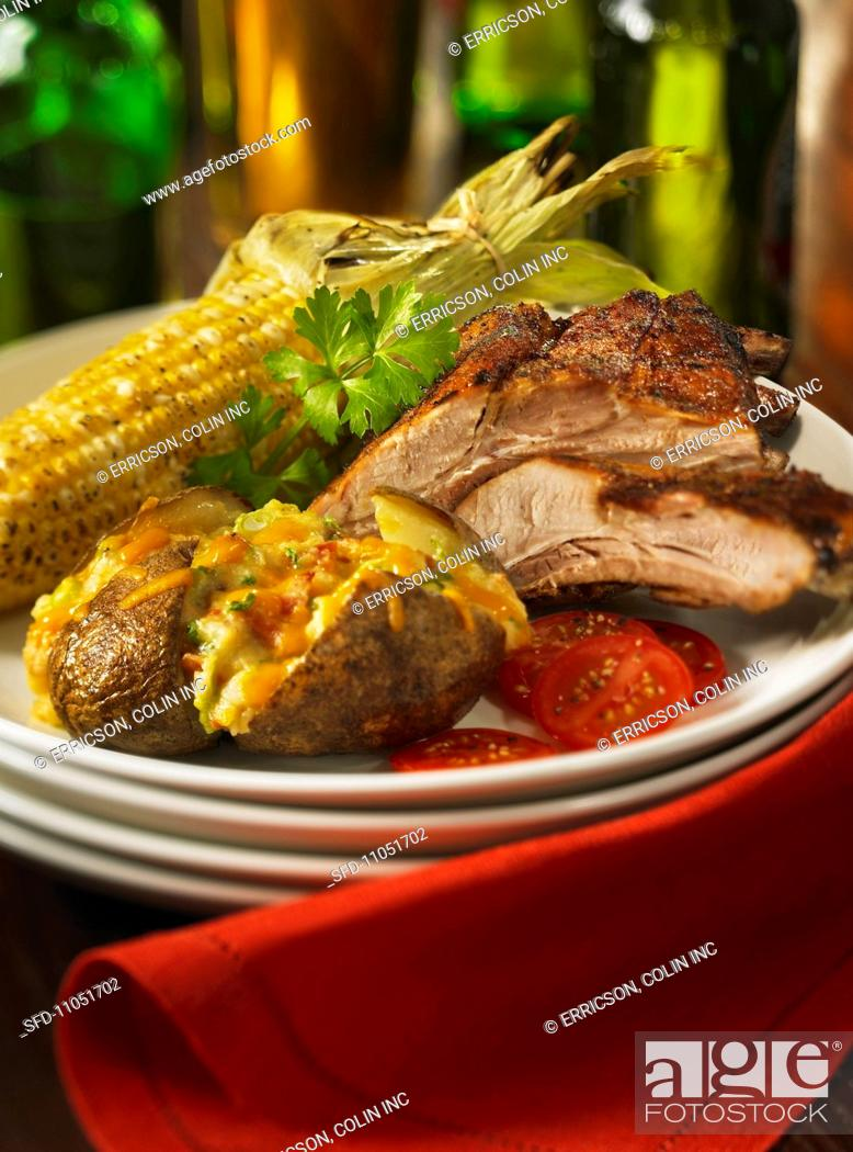 Stock Photo: A grill platter with spare ribs, baked potatoes with Cheddar cheese and corn cobs.