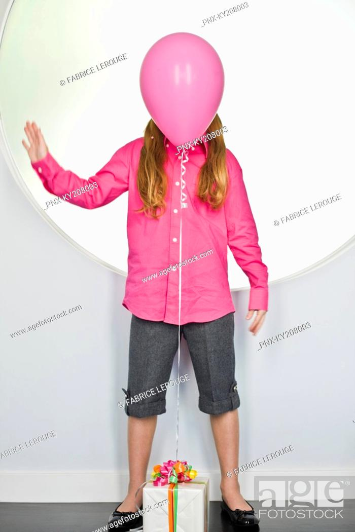 Stock Photo: Pink balloon tied with a birthday present in front of a girl's face.