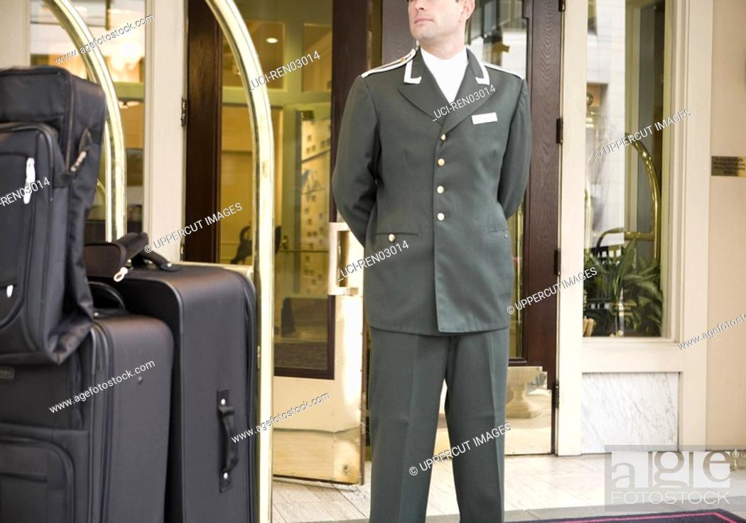 Stock Photo: Bellhop standing next to luggage cart.