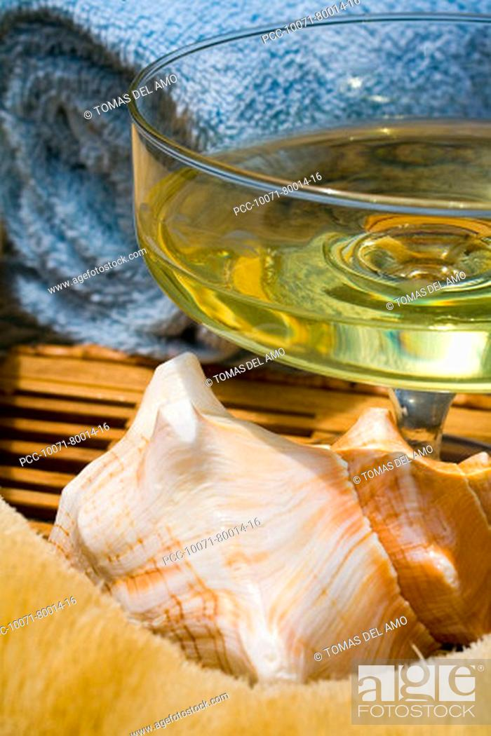 Stock Photo: Spa elements, glass filled with yellow liquid, with seashell, towel and natural loofah.