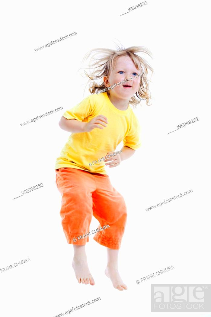 Stock Photo: energetic boy jumping in the air - isolated on white.