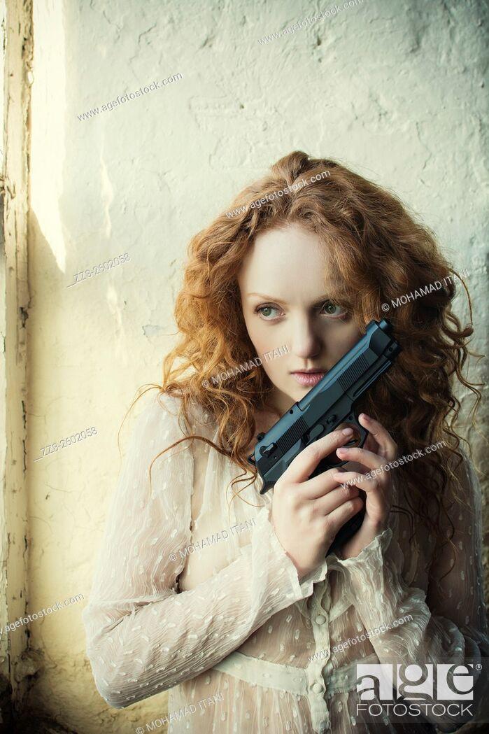 Stock Photo: Redhead woman holding a gun.