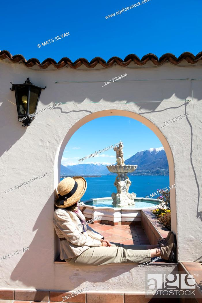 Imagen: Woman with straw hat relax in an arch with a water fountain over alpine lake Maggiore with snow-capped mountain in a sunny day in Ticino, Switzerland.