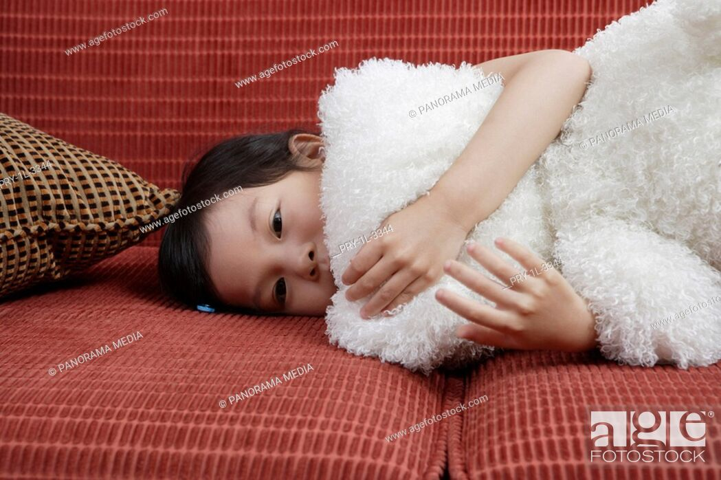 Imagen: Girl lying in sofa with doll.