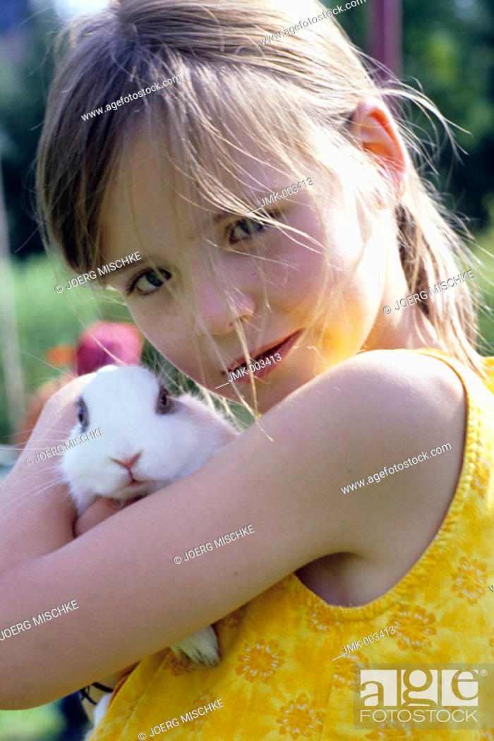 Stock Photo: Portrait of a girl, 5-10 years old, in the garden in summer, holding a rabbit, bunny in it's arms.