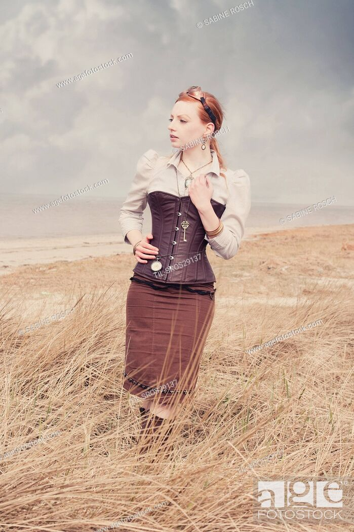 Stock Photo: Young woman with red hair wearing goggles and corset standing alone outdoors beside the sea.