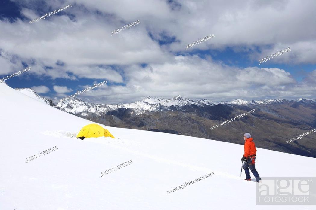 Stock Photo: Hiker walking toward tent in snowy mountains.