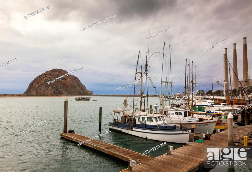 Stock Photo: Boats tied up to the dock in Morro Bay, with Morro Rock in the background; California, United States of America.