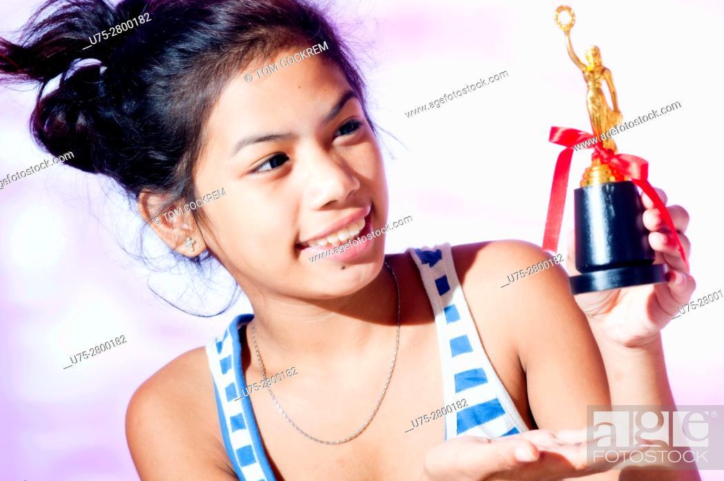 Stock Photo: Teenage girl athletics trophy in studio setting.