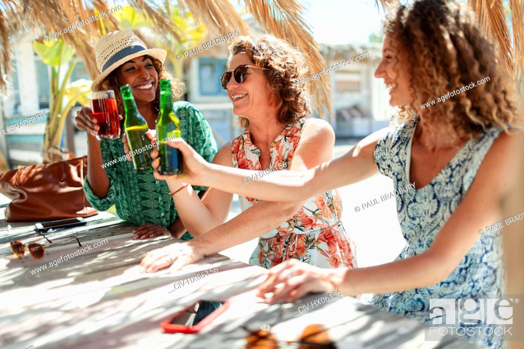 Stock Photo: Happy women friends drinking cocktail and beer at sunny beach bar.