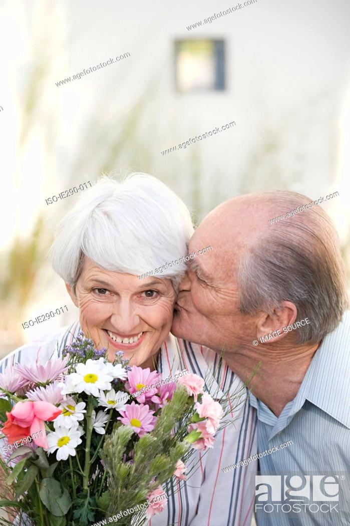 Stock Photo: A senior man kissing a senior woman on the cheek.